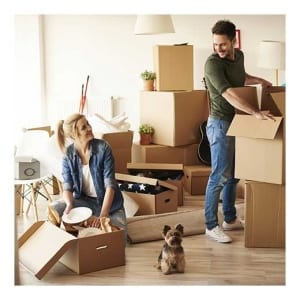 Couple moving boxes into new apartment with dog